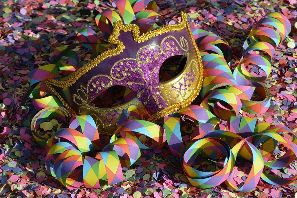 Fasching: Luftschlange und Maske auf Konfetti