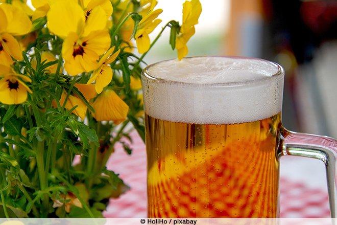Ein Glas Bier und gelbe Blumen auf einer karierten Tischdecke