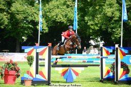 Ein Pferd springt bei einem Turnier über ein Hinternis.