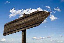 Führungen: Wegweiser aus Holz vor blauem Himmel zeigt nach rechts