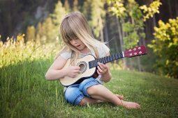 Musik für Kinder: Ein Mädchen sitzt auf einer Wiese und spielt Gitarre